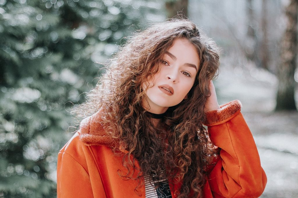 A girl in a red coat with curly hair