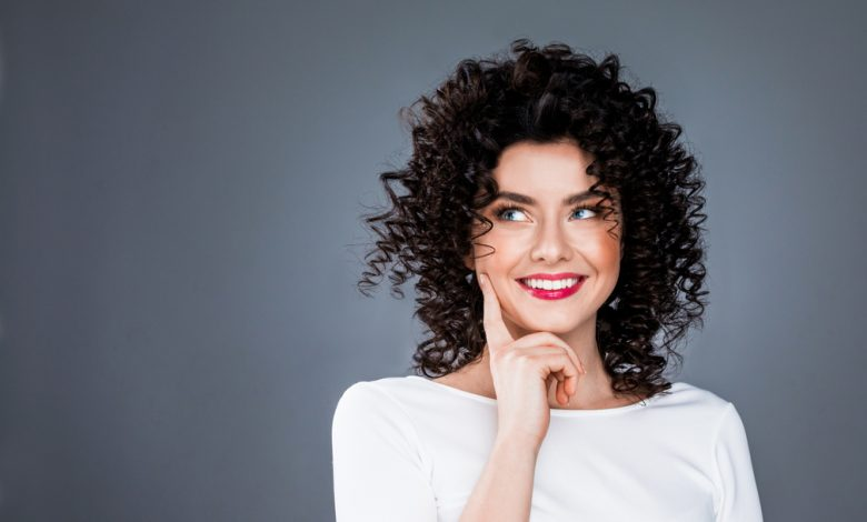 A smiling woman with shiny curly hair