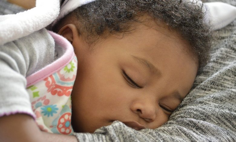 A baby with curly hair sleeping in her mothers arms