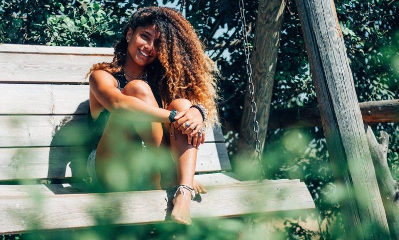 A girl with dyed curly hair sat on a bench