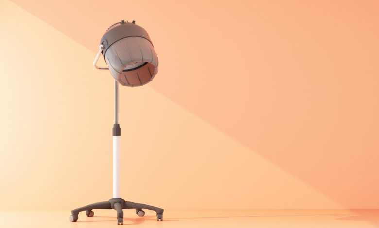 A hooded hair dryer in a peach coloured room