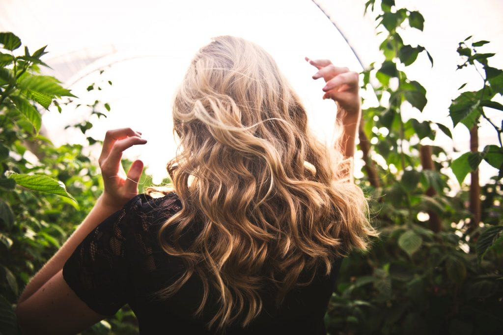 Woman with blonde curly hair in a field