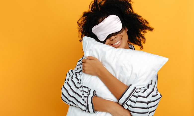 A curl haired woman holding a pillow