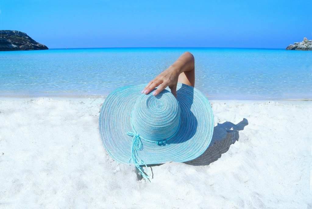 A woman on the beach wearing a sun hat