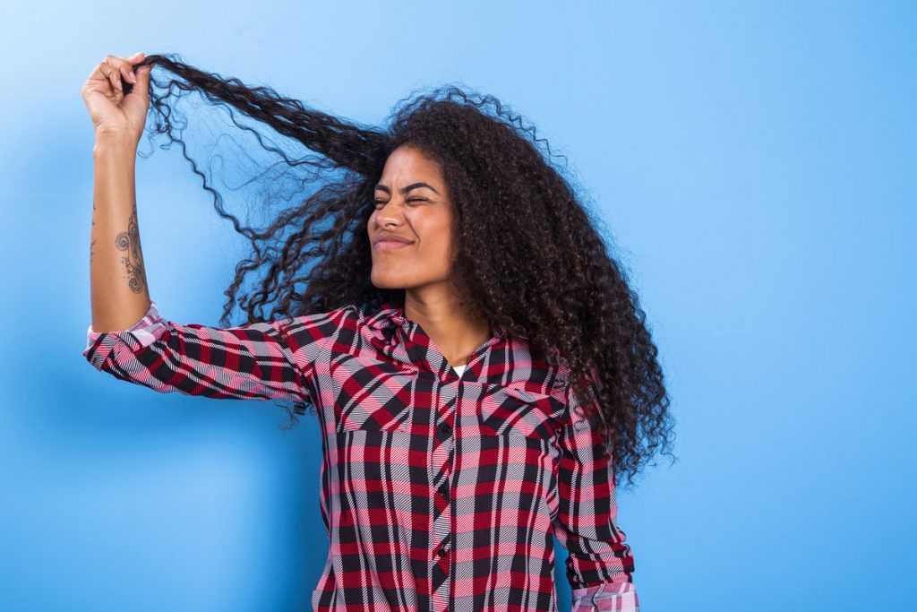 A woman looking worriedly at her frizzy hair
