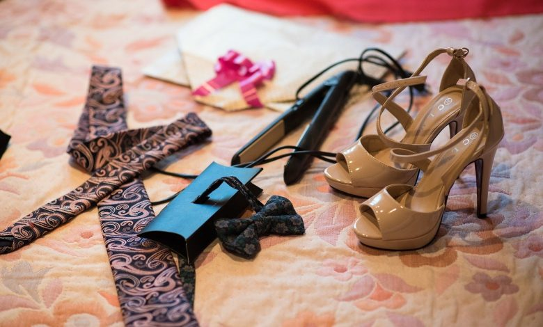 Hair straighteners on a bed next to shoes and clothes