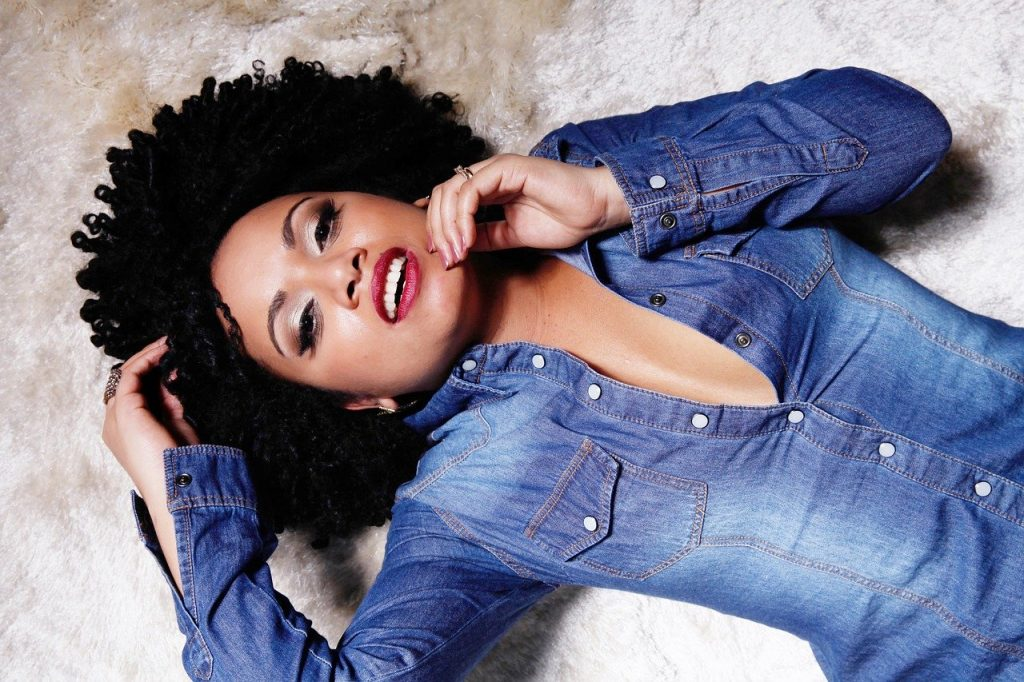 A woman with curly hair wearing a denim shirt