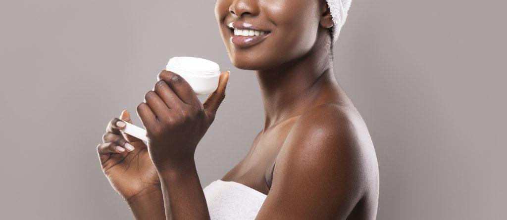 A woman holding a tub of hair moisturiser
