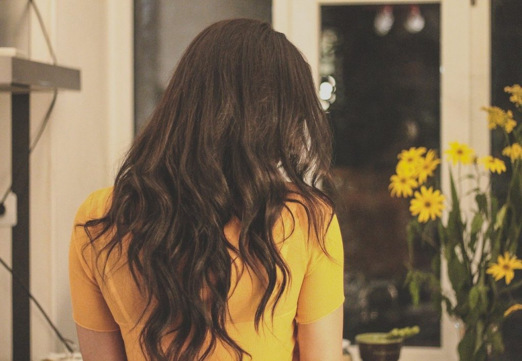 A woman with curly hair in a yellow shirt