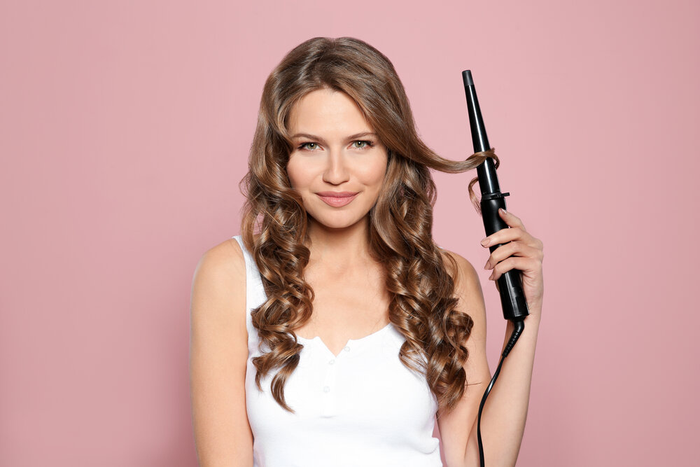 A woman curling her hair