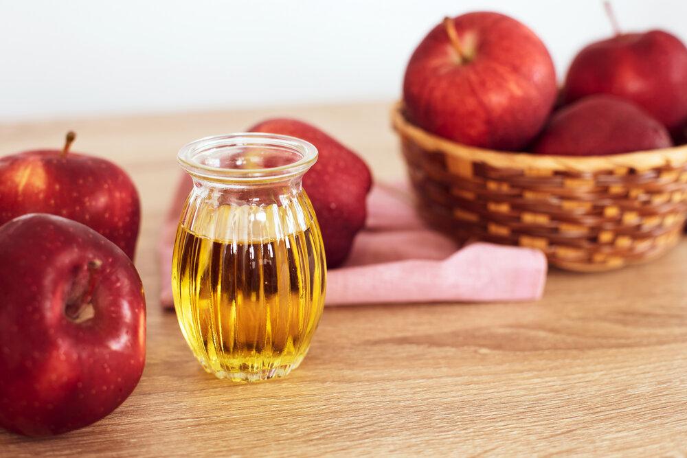 A jug of apple cider vinegar next to apples