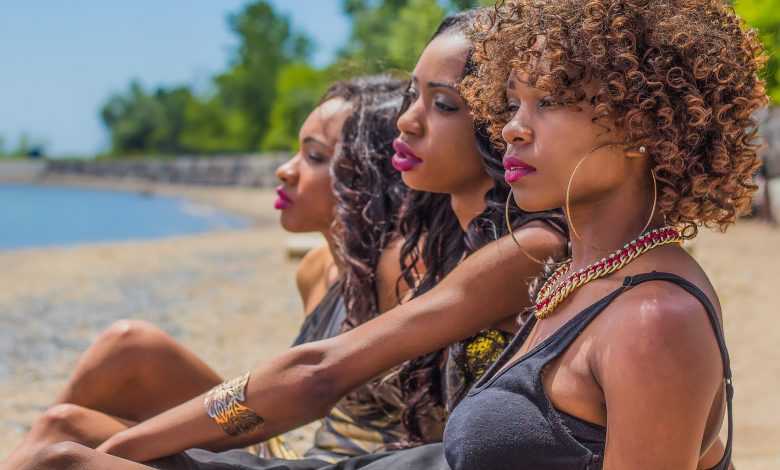 Three curly haired ladies sat on the beach