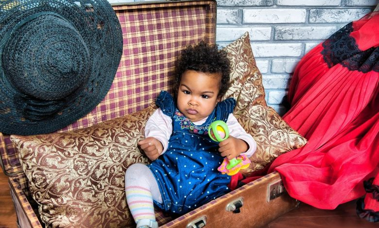 A toddler with curly hair sat in a chest
