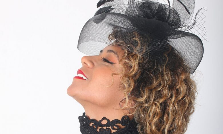 A woman with curly hair wearing a fascinator