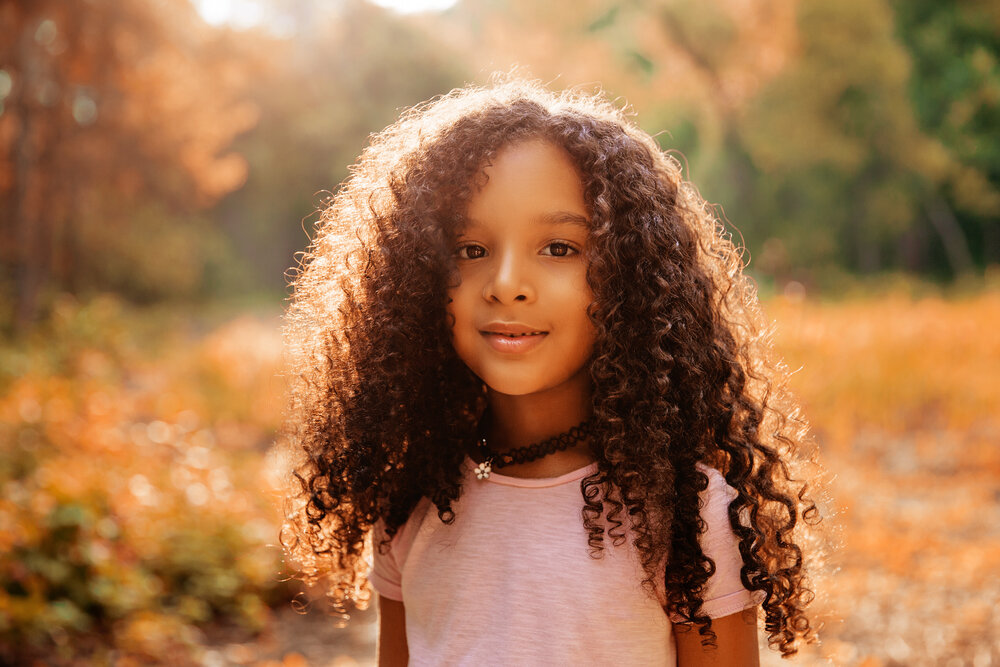 A young girl with curly hair outside