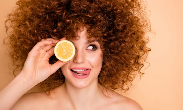 A woman with curly hiar holding a lemon over her eye
