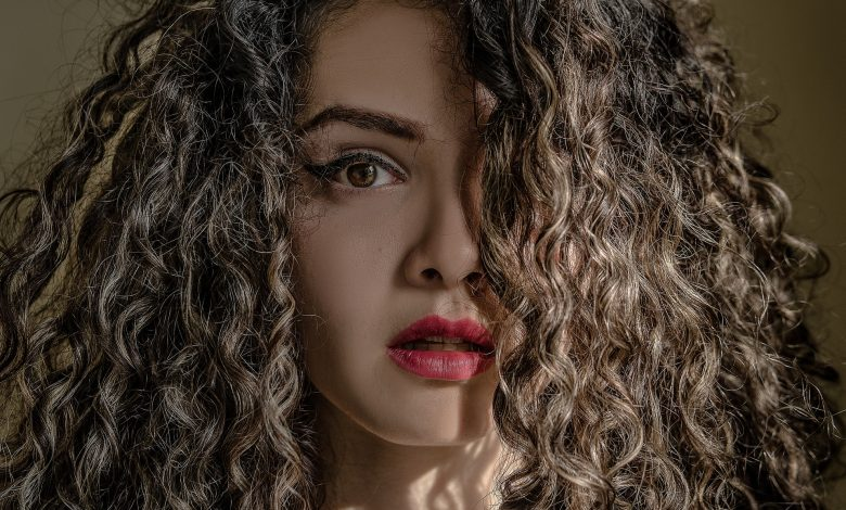 A woman with How to Care for Low Porosity Curly Hair