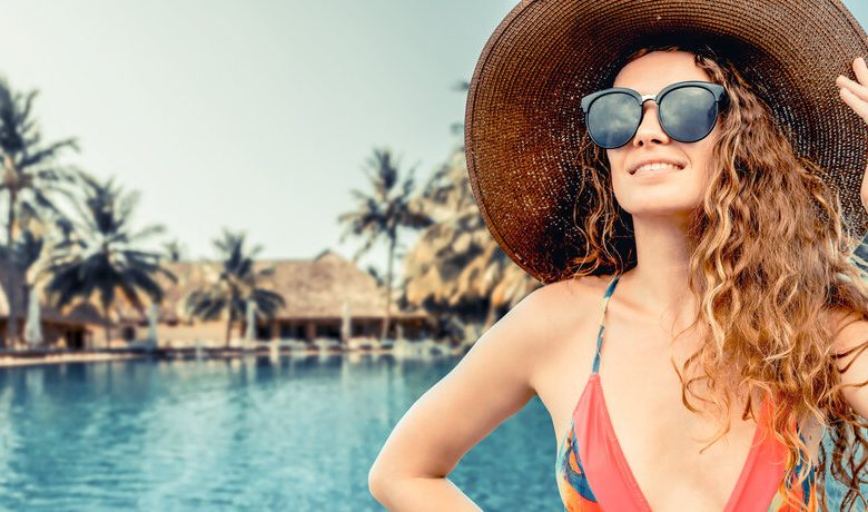 A woman weaing a hat next to a swimming pool